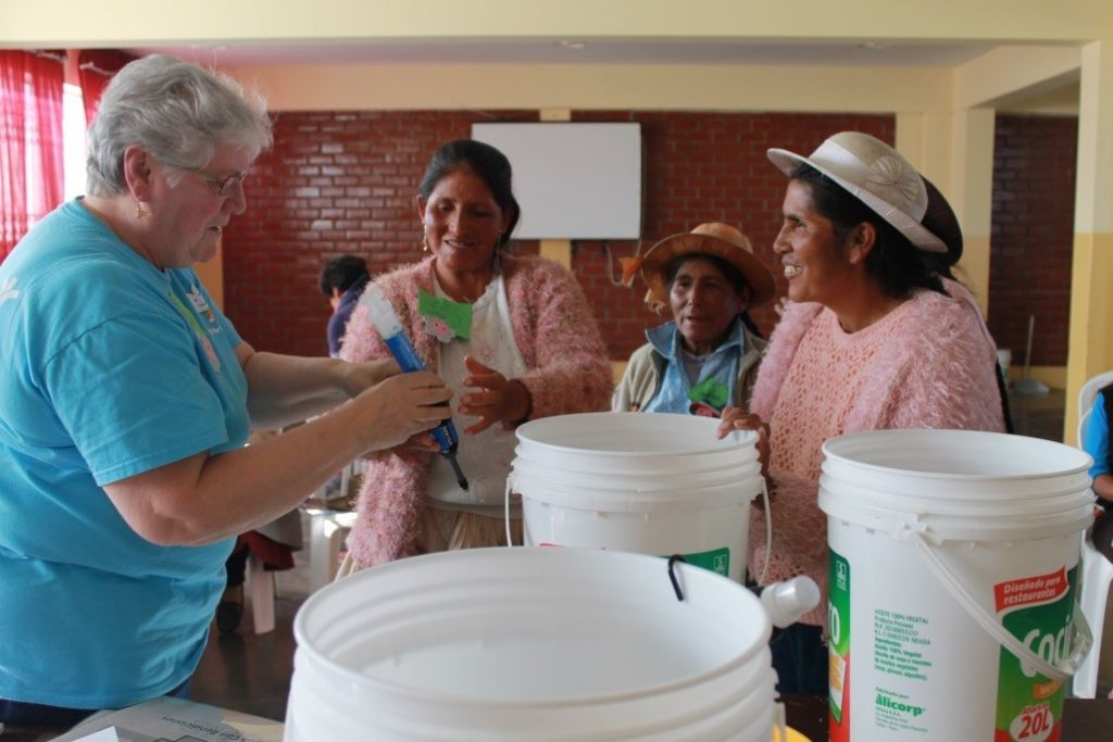 "Sister Fran Gorsuch demonstrates the ""Water With Blessings"" project to  Peruvina women"